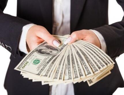 אדם בחליפה מגיש כסף מזומן כהלוואה