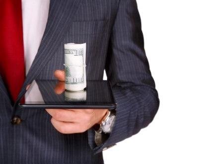 אדם מחזיק טאבלט ושטרות כסף