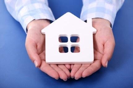 אדם מחזיק דגם של בית בידיו