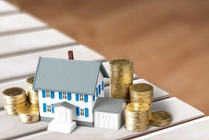 דגם של בית ומטבעות כדוגמה לשיעבוד נכס לצורך הלוואה
