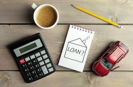דף עם כיתוב הלוואה ליד דגם מכונית, כוס קפה, עיפרון ומחשבון